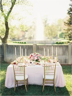 Sweetheart table with gold chairs, elegant gold candlesticks, and a gorgeous blush, pink and cream rose floral arrangement as centerpiece