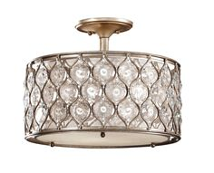 The Lucia lighting collection is a completely fresh, contemporary take on crystal light fixtures.  The unique, disk-shaped Sunflower Shape Bauhinia crystals are suspended within the intricate metal work presented in a Burnished Silver finish, which combine to create these sleek profiles surrounding inner Linen drum shade.  The Leila lighting collection is a sister style, utilizing the same crystals and metal work in orb and sunburst silhouettes.