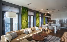 Ukranian studio apartment with green living walls. Very cool space. Love the long sofa and the wooden trunk coffee table. I think the green walls add a lot to the space