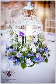 White birdcage with led candle and wreath of blue and white hydrangeas in the middle. Beautiful centrepieces