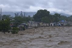 Heavy rains from Hurricane Sandy causes the Croix de Mission river to swell to levels that threaten to flood the homes along its bank in Port-au-Prince October 25, 2012. According to media reports Hurricane Sandy has claimed one life in Haiti. REUTERS/Swoan Parker (HAITI - Tags: DISASTER ENVIRONMENT TPX IMAGES OF THE DAY)