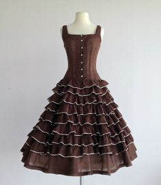 Whimsical 1950s brown dotted swiss party dress. Fitted bodice. Square neckline. New look silhouette. Full tea length skirt with layers of soft ruffles.