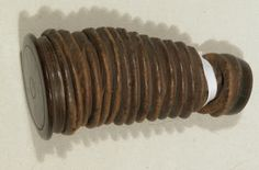 Wig powderer, 18thC - Made from polished wood and brown leather with traces of powder inside. It is a truncated cone of leather on a metal spiral. At the smaller end there is a ring of wood with a fine metal mesh over a central hole. The wider end is a wooden disc that unscrews to open.