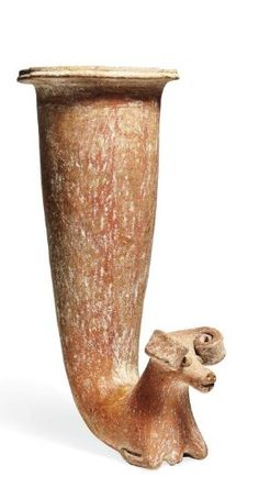 Parthian pottery ram headed rhyton, 3rd-1st century B.C.   Of trumpet form, terminating in the forequarters of a ram with curling horns, slit-like mouth, applied circular eyes, and a pouring spout between the bent forelegs, with remains of red painted vertical bands of triangular and scrolling decoration down the front of the vessel, 28 cm high. Private collection