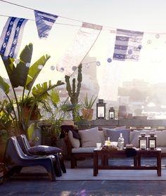 屋上テラスに設置した、クッションを置いた3人掛けソファとコーヒーテーブル。