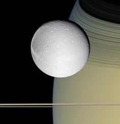 The Cassini spacecraft took this view of Saturn's moon Dione in October 2005, with the tranquil gold and blue hues of Saturn in the distance. The horizontal stripes near the bottom of the image are Saturn's rings