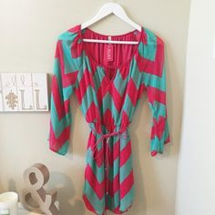 Pink & Mint Chevron Dress This beautiful hot pink and mint green chevron dress is so comfy and cute! Brand new! Perfect if you're on the shorter side!   Sheer long sleeves  Has a slip underneath   Ties at the waist  Small cutout right under the neck   Stretchy waist  Very flattering!   100% polyester a'gaci Dresses