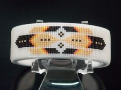 American Indian Beaded Bracelet with a Frosted Crystal Background. The Phoenix Design is created using soft red, orange and yellow with tan and black feathers.