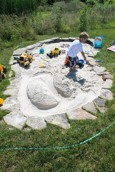 Husband built this kidney shaped stacked flagstone sandbox. It's approximately 7'x13'. Perfect option for an area that is not level. The ground toward the tall grass in the picture is actually 1.5feet lower than the tallest end. The sandbox actually looks like a nice addition to the backyard:)