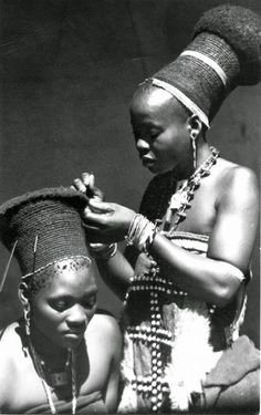 Young Zulu woman having her hair or headdress done. South Africa. ca. early to mid 20th century.