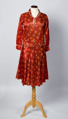 Dress ca 1926  A mid brown evening dress made of rayon taffeta with a print of tan and fawn leaves and fawn flowers.
