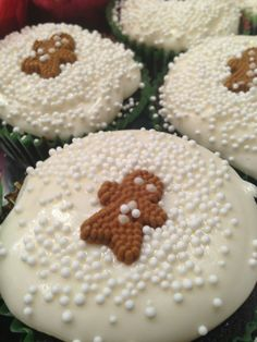 Gingerbread cupcakes with cream cheese frosting, white sprinkles, and Wilton gingerbread candies
