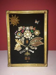 Beautiful handmade framed art made from vintage costume jewelry. Frame measures 5x7. Background is black velvet cloth. Please contact me with any questions. Thank you for shopping
