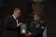 Deputy Defense Secretary Bob Work presents the Medal of Honor flag to former Army Sgt. Kyle J. White, the most recent Medal of Honor recipient, during a ceremony to induct White into the Hall of Heroes at the Pentagon, May 14, 2014. President Barack Obama awarded White the medal for courageous actions while serving as a platoon radio telephone operator during combat operations against an armed enemy in Afghanistan's Nuristan province, Nov. 9, 2007. DOD photo by Marine Corps Sgt. Aaron…