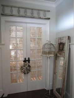French doors with burlap and gorgeous old bird cage and shabby old mirror-door!