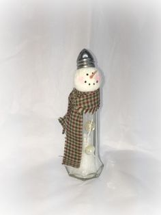 Eiffel tower glass salt shaker has been used to create his body. Faux snow and glitter added to his tummy. He has vintage buttons attached to the front of his body. His hat is the salt shaker cap. Scarf fabric will vary for the homespun. The white fabric has gold metallic Star of Bethlehem scattered throughout.   The perfect gift for the person who has everything.  Dimensions are approx at: 5.75 X 1.75  Since each is individually handmade, no two will be alike. From a smoke free, feline…