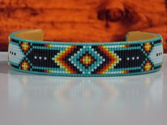 Native American Beaded Cuff Bracelet With A Cherokee Chevron Pattern in the traditional Cherokee colors of green turquoise, black, red, orange, yellow and white The base used for this bracelet is bras Beaded Cuff Bracelet, Bead Loom Bracelets, Beaded Bracelet Patterns, Jewelry Patterns, Native American Beadwork, Native American Jewelry, Native Beadwork, Seed Bead Patterns, Beading Patterns