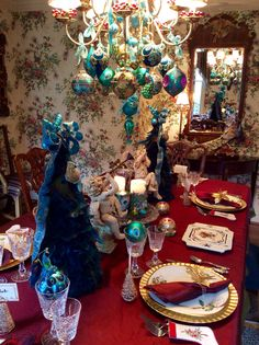 Formal dinning room, Birds of a Feather, peacock themed Christmas tablescape drawn from peacocks in wallpaper and Fitz and Foyd large figurine on side table. Peacocks featured in two large feathered trees, ornaments and ribbon draped chandelier, candles, and flatware.