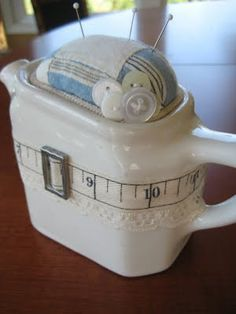 Small vintage pitcher, quilt scrap, embellishments, and - Voila!  A very cute pin cushion!  from mamiejanes.blogspot.com