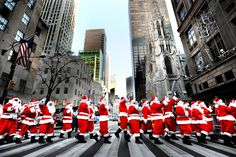 christmas in new york | Volunteers dressed as Santa Claus cross New York's Fifth Avenue as ...
