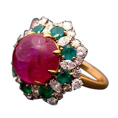 A beautiful ring, manufactured by Bulgari in the 1970s, presenting a cabochon ruby weighing approximately 10cts, enriched by emeralds (appr. 2 cts) and diamonds (app. 2 cts), mounted in 18kt yellow gold.