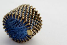 Made from blue zipper with golden teeth.  Diameter is 1.8 centimeters (0.71 inches) and height is 2 centimeters (0.79 inches).