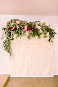 DIY Photo Backdrop with faux florals, greenery and a SHOWER CURTAIN! Wow! SO smart! Love this idea!