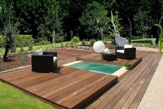 inground swimming pool-spa with wood cover. Saw similar picture years ago with a pool that was otherwise used as an entertaining deck