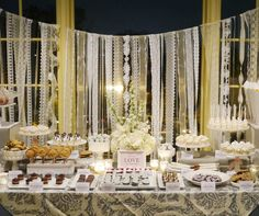 A patterned tablecloth and curtain of differing white ribbons illuminates this stunning wedding dessert table.