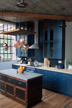 In love with this dark kitchen with blue cabinets + copper accessories | Taylor + Taylor