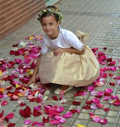 Una damita de honor rodeada de petalos y coronada con una preciosa coronita. Encuentralo en www.pettyperezmanglano.com