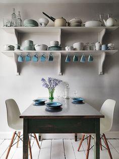 szaro-turkusowa kuchnia,aranzacja kuchni w mieszanym stylu,stół turkusowy vintage,turkusowe akcesoria kuchenne,kubki i talerze w turkusowym kolorze,skandynawska kuchnia z turkusową porcelaną i stołem,drewniany stół prostokatny w turkusowej patynie,postarzany trkusowy stół,bałe nowoczesne krzesła VITRA w kuchni,kuchenne półki z turkusowymi dekoracjami