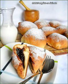 Ingrediente: 500 g faina, 1 praf de sare, 3 linguri zahar, 1/4 l lapte, 1 cub drojdie proaspata(30 g), coaja rasa de la 1 lamaie, 170 g unt moale, 1 ou, dulceata, grasime pentru forma, zahar pudra pentru decorat, Preparare: Se pune faina intr-un castron,se presara sarea si zaharul pe deasupra. Se face o adancitura