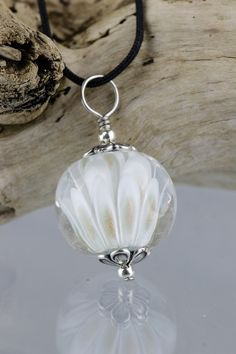 "Petals of a delicate white with flecks of gold encased in clear glass. Reminiscent of a beautiful lotus flower. The lotus flower is legendary in Greek mythology inducing dreamy forgetfulness and an unwillingness to depart. A roundish pendant with smooth surface measuring 19 mm (3/4"")."