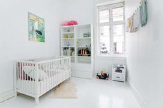 Scandinavian, modern, neutral nursery decor. White floors, Tintin poster, Brio play kitchen. Toddler or baby girls room.