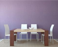A minimalistic dining area with pastel purple wall, rectangular wooden table for four, white chairs, and a rustic rattan rug. Purple Bedroom Walls, Purple Bedroom Design, Purple Bedrooms, Purple Interior, Bedroom Designs, Dining Room Paint Colors, Dining Room Design, Dining Area, Light Purple Rooms