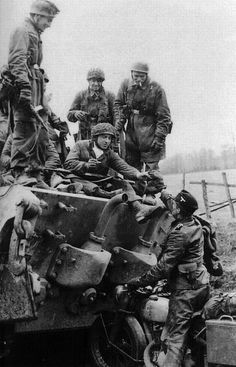 German paratroopers (Fallschirmjäger) share a smoke with the crew of a King Tiger tank somewhere in France, 1944. *Note the huge towing hooks on either side of the tank's chassis!