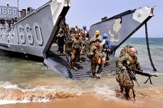 U.S. Marines disembark a landing craft during an offload of U.S. Navy Seabees and Spanish, Portuguese and British marines to Naval Mobile Construction Battalion 7 in Guereo, Senegal, April 6, 2010. The Marines and Seabees will work with the Senegalese army as part of Africa Partnership Station West, an international initiative developed by U.S. Naval Forces Europe and U.S. Naval Forces Africa to to improve maritime safety and security.