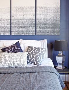 A boutique hotel inspired bedroom with bold blue painted walls and lots of textiles.