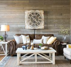 Farmhouse living room. A light and airy look with a brown sofa, warm white tables, mix of textures and gray rustic wood wall