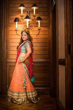 A peach & teal Lehenga choli by Sabyasachi for the Mehendi ceremony of Poonam Jeswani of WeddingSutra.