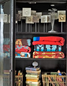 """Shelves of an armoire brim with wood corner blocks treated as sculpture and folded Pendleton blankets. """"In collections, common objects can become art,"""" says Robin Long Mayer."""