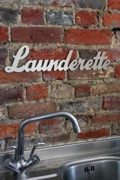 #metal #sign. I Love the contrast of the smooth brushed steel on rugged brick. Design ideas for metal signs. Launderette