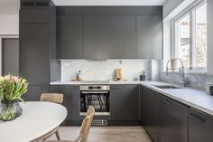 Kök från Ballingslöv med bänkskivor och stänkskydd i massiv carrara-marmor. Kökslucka Solid i peppargrått och handtag med grå strukur.