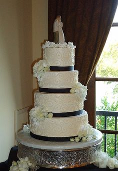 Ivory buttercream wedding cake with black satin ribbon and scroll work