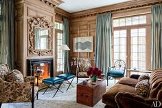 Rift-sawn white oak panels the library of this California family home, decorated by Miles Redd. Stools in a Moore and Giles fabric stand before the fireplace; a framed textile by Natural Curiosities is displayed near the French doors.
