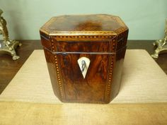 George III Burr Yew Wood Octagonal Tea Caddy, the edges inlaid with chequeured and line stringing, the front side with a diamond escutcheon.  The interior with a compartment lid inlaid as per the body. c 1750 from Mytton Antiques