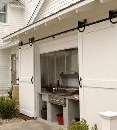 Built in Grill carriage house sliding doors. (I want this in my dream home! What a great way to keep an outdoor kitchen out of the elements! Outdoor Rooms, Outdoor Living, Outdoor Kitchens, Indoor Outdoor, Outdoor Grill Area, Outdoor Grilling, Outdoor Cooking, Bbq Area, Outdoor Laundry Area