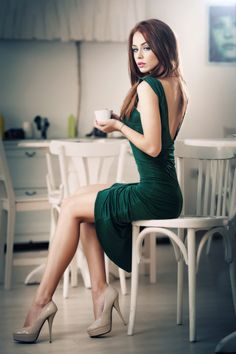Resting her long legs for a spot of tea wearing a green dress and nude platform heels