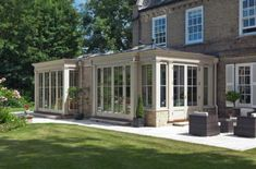 An impressive extension which creates 2 rooms. Full length panelling maximises light and sets of double doors open the conservatory to the patio and garden. Georgian Kitchen, Georgian Homes, Victorian Homes, Orangerie Extension, Conservatory Extension, Kitchen Orangery, House Extensions, Kitchen Extensions, House With Porch